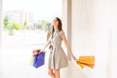Woman and shopping. Young woman with bags in shopping center, smiling and  walking Royalty Free Stock Photography