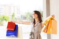 Woman and shopping. Young woman with bags in shopping center, smiling and  walking Royalty Free Stock Photos