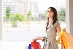 Woman and shopping. Young woman with bags in shopping center, smiling and  walking Royalty Free Stock Images