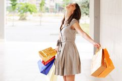 Woman and shopping. Young woman with bags in shopping center, smiling and  walking Stock Photo