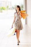 Woman and shopping. Young woman with bags in shopping center, smiling and  walking Royalty Free Stock Photo