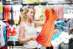 Woman shopping apparel clothes. Woman choosing dress during shopping at garments apparel clothing shop Royalty Free Stock Photos