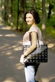 Woman with shopping bag. Happy brunet woman with shopping bag, outdoors Royalty Free Stock Images