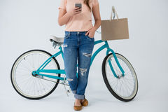 Woman with shopping bag and bicycle using mobile phone Royalty Free Stock Image