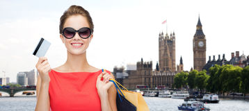 Woman with shopping bag in and credit card london. People, holidays, tourism, travel and sale concept - young happy woman with shopping bags and credit card over Stock Images