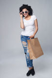 Woman with shopping bag. Full length happy fashionable woman holding craft shopping bag with empty copy space on grey background Royalty Free Stock Photo