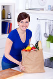 Woman with shopping bag in the kitchen Royalty Free Stock Photo