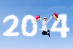 Woman with shopping bag and New Year 2014. Asian woman with shopping bag is jumping announce Happy New Year 2014 Royalty Free Stock Photo