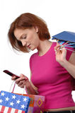 Woman with shopping bags. And cell phone on a white background Royalty Free Stock Photo