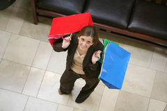 Woman with shopping bags. Overhead view of attractive young woman with red and blue shopping bags Royalty Free Stock Photo