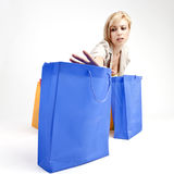 Woman with shopping bags. Attractive young woman reaching out towards blue shopping bags, isolated on white background Stock Photography