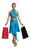 Woman with Shopping Bags. Young blonde woman in a fancy dress with shopping bags walking to the camera against a white background Stock Images