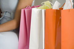 Woman with shopping bags. Partial profile of a woman in a blue dress sitting with colourful shopping bags next to her Royalty Free Stock Image