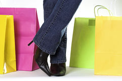 Woman and shopping bags. Woman standing with colorful shopping bags with legs crossed royalty free stock image