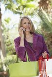 Woman with Shopping Bags and Cell Phone Stock Photography