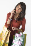 Woman with shopping bags and cellular phone. Pretty young woman with shopping bags and cellular phone Royalty Free Stock Image