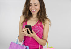 Woman with shopping bags checking her cell phone Stock Image