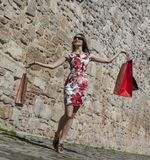 Woman with Shopping Bags in a City. Happy young woman with shopping bags in a small street of an old city Royalty Free Stock Image