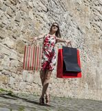 Woman with Shopping Bags in a City. Happy young woman with shopping bags in a small street of an old city Stock Photo