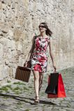 Woman with Shopping Bags in a City. Young woman with shopping bags walking in a small street of an old city Stock Photos