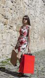Woman with Shopping Bags in a City. Young woman with shopping bags walking in a small street of an old city Royalty Free Stock Photo