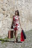 Woman with Shopping Bags in a City. Young woman with shopping bags walking in a small street of an old city Royalty Free Stock Image