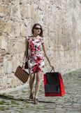 Woman with Shopping Bags in a City. Young woman with shopping bags walking in a small street of an old city Stock Photo