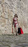 Woman with Shopping Bags in a City. Young woman with shopping bags walking on a small street of an old city Royalty Free Stock Images
