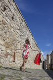Woman with Shopping Bags in a City. Young woman with shopping bags walking on a small street in an old city Royalty Free Stock Photography