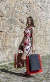 Woman with Shopping Bags in a City. Young woman with shopping bags posing in a small street of an old city Royalty Free Stock Photo