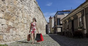 Woman with Shopping Bags in a City. Young woman with shopping bags walking on a small street of an old city Stock Photography