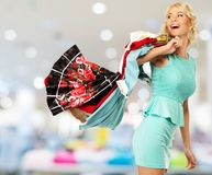 Woman with shopping bags in clothing store Stock Photography