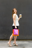Woman with shopping bags and coffee in the city Royalty Free Stock Photography
