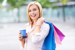 Woman with shopping bags and coffee to go Royalty Free Stock Photography