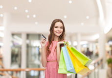 Woman with shopping bags and credit card in mall. Sale, consumerism, money and people concept - happy young woman with shopping bags and credit card in mall Stock Photos