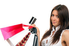 Woman with shopping bags, credit gift card. Pretty young woman with shopping bags, credit gift card in one hand buying presents, smiling and looking at the Royalty Free Stock Photos