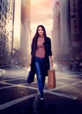 Woman with shopping bags crossing a city street Royalty Free Stock Images