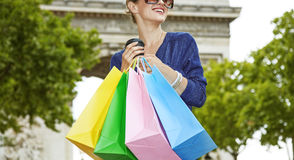 Woman with shopping bags and cup of coffee looking into distance Stock Photography