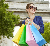 Woman with shopping bags and cup of coffee looking into distance Royalty Free Stock Photos