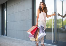 Woman with shopping bags entering shop Stock Photo