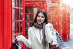 Woman with shopping bags in front of red telephone booths in London, UK royalty free stock photography