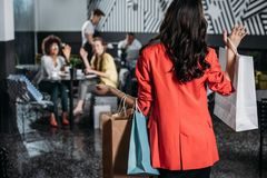 Woman with shopping bags going to her friends. In cafe stock photos