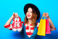 Woman with shopping bags and gumshoes Stock Images