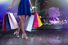 Woman with shopping bags in hand walks in the city stock images