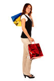 Woman shopping, bags high. Looking. Beautiful woman is done with shopping, two bags are raised to the head level. Isolated stock photography