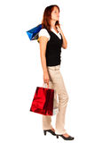 Woman shopping, bags high. Looking to the side. Beautiful woman finished shopping, two bags are raised to the head level. Looking to the side. Isolated royalty free stock image