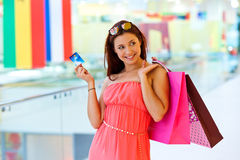 Woman with shopping bags holding credit card. Attractive woman with shopping bags holding credit card Royalty Free Stock Photo