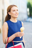 Woman with shopping bags and ice cream in city Stock Images