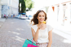 Woman with shopping bags and ice cream in city Stock Photo