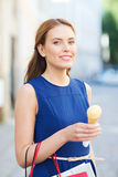 Woman with shopping bags and ice cream in city Stock Image
